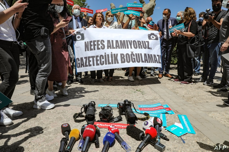 """People stand behind a banner reading in Turkish """"We can't breath. Journalism cannot be drowned!"""" during a rally outside the…"""