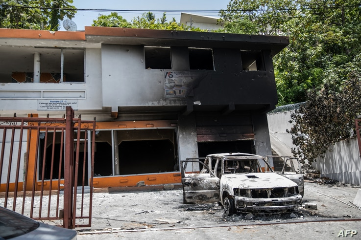 A charred car and building are pictured near the Petionville Police station after incidents, where suspects of being involved...