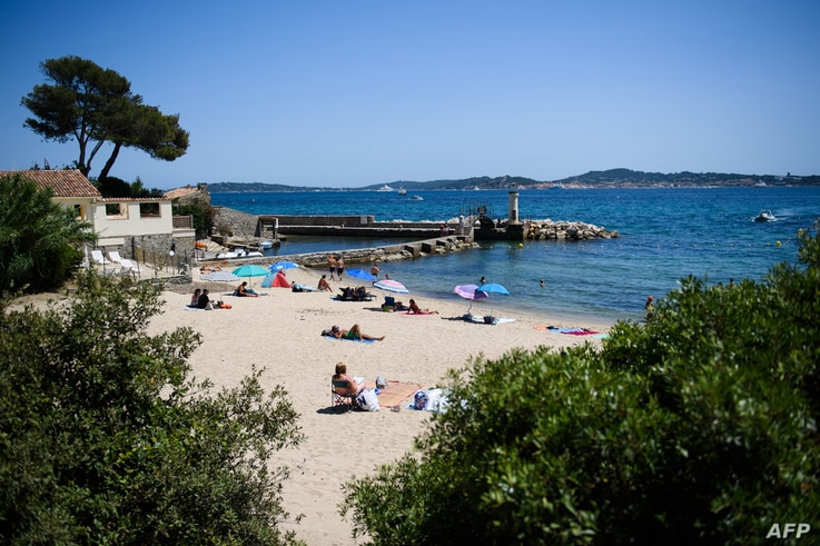 """People swim and enjoy a sunny day at """"Les Cigales"""" beach in Port-Grimaud, with Saint-Tropez in the background, southern France…"""