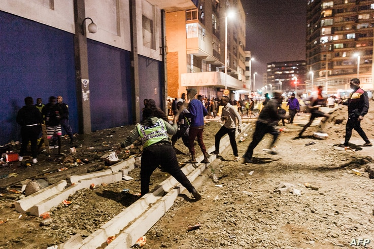 South Africa Police Services (SAPS) officers stop looters from looting in central Durban, on July 11, 2021. - Several shops are…