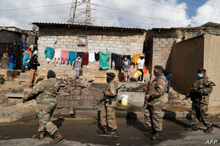 People stand near their home and watch as members of the South African Defence Force (SANDF) patrol their area in Alexandra…