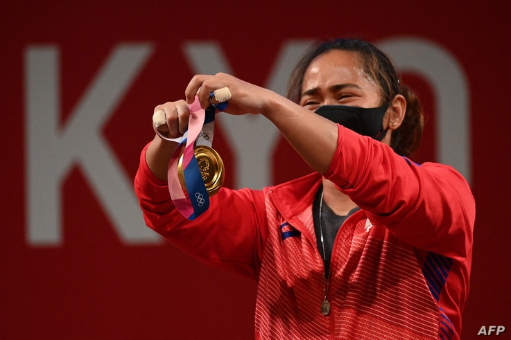 Gold medallist Philippines' Hidilyn Diaz holds her medal on the podium for the victory ceremony of the women's 55kg...