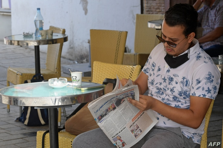 A Tunisian man reads the newspaper on the Habib Bourguiba avenue in Tunis on July 27, 2021. - Tunisia, the birthplace of the...