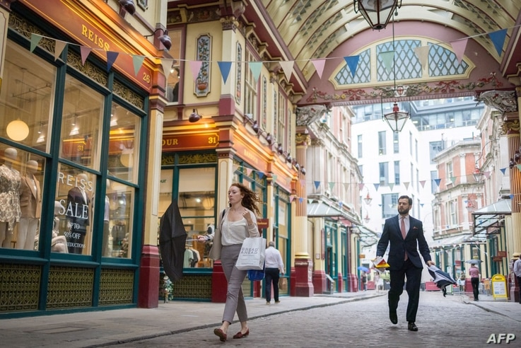 People walks past shops and restaurants at Leadenhall Market in the City of London on July 27, 2021. - Prime Minister Boris…