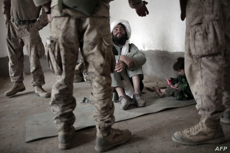 A local Afghan imam listens to an interpreter for US Marines of India Company, 3rd Battalion, 6th Marines, before receiving 20…