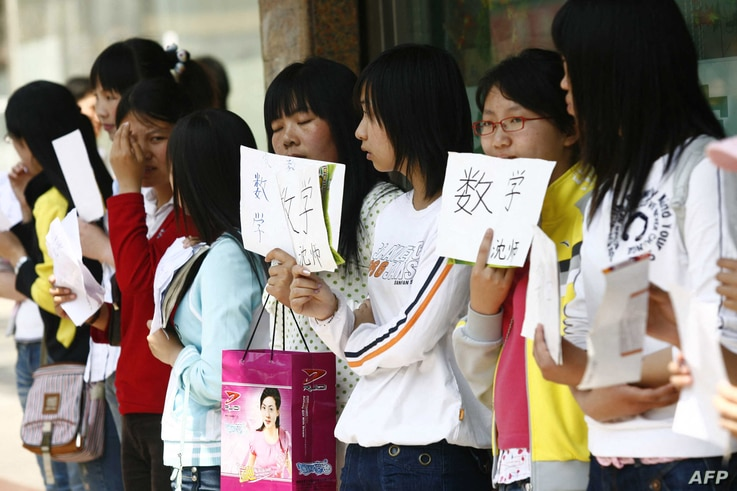 A group of unemployed Chinese graduates hold signs offering themselves as tutors, along a street in Shenyang, northeast China's…