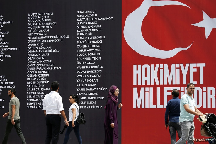 People make their way next to a banner reading the names of civilians and policemen who were killed while resisting the coup…
