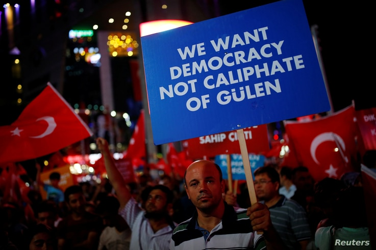 A man holds a banner as he and others have gathered in solidarity night after night since the July 15 coup attempt in central…