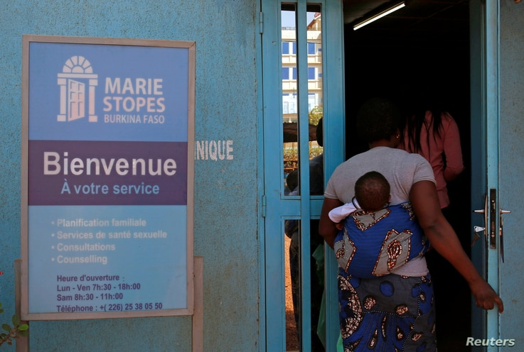 A woman carrying a baby arrives at the clinic of the NGO Marie Stopes in Ouagadougou, Burkina Faso February 16, 2018. Picture...
