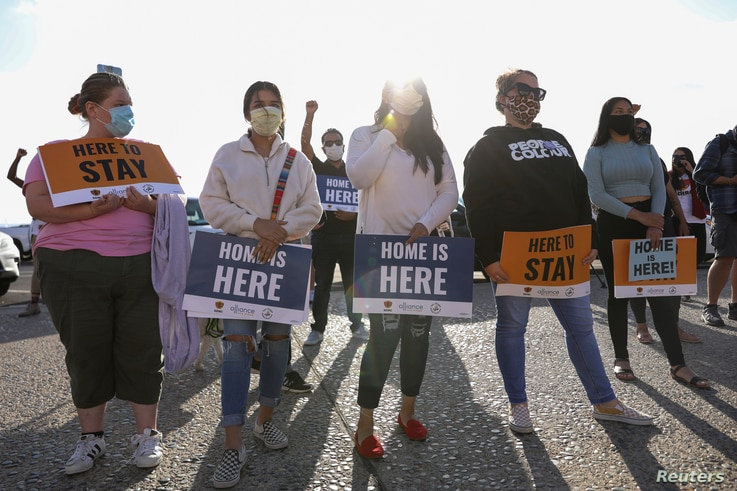 FILE - People hold signs as they take part in a rally for 'Justice Everywhere' to celebrate the U.S. Supreme Court's ruling to disallow the rescinding of the Deferred Action for Childhood Arrivals (DACA) program, in San Diego, California, June 18, 2020.