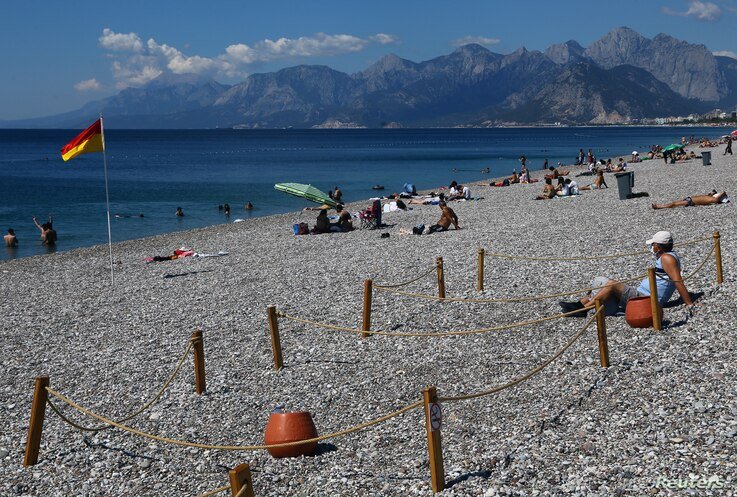 A man sits in an area marked by cordons of ropes and wooden stakes to enforce social distancing measures on the Konyaalti beach…