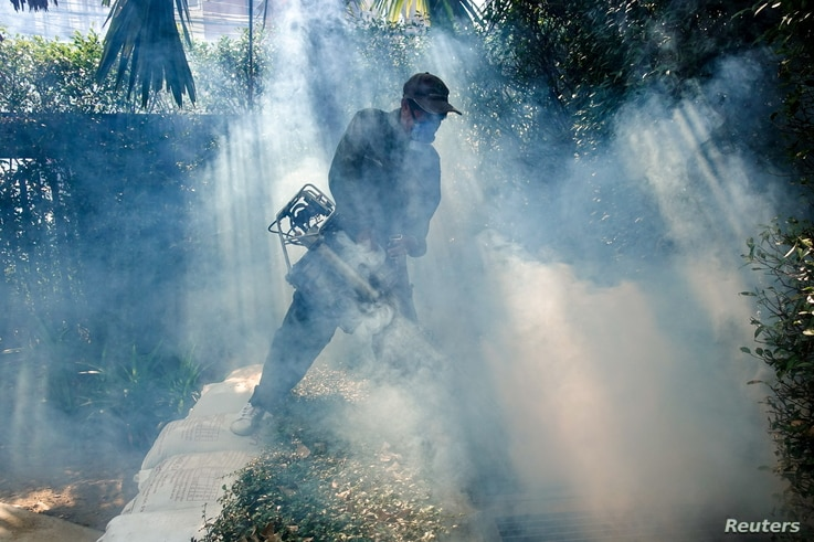 FILE PHOTO: A worker sprays insecticide for mosquitos at a village in Bangkok, Thailand, December 12, 2017. Picture taken…