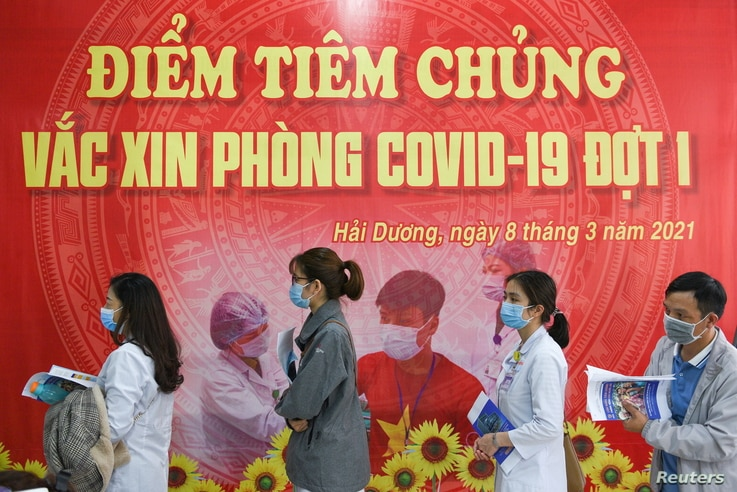 FILE PHOTO: Health workers wait for their turn as Vietnam starts its official rollout of AstraZeneca's coronavirus disease …