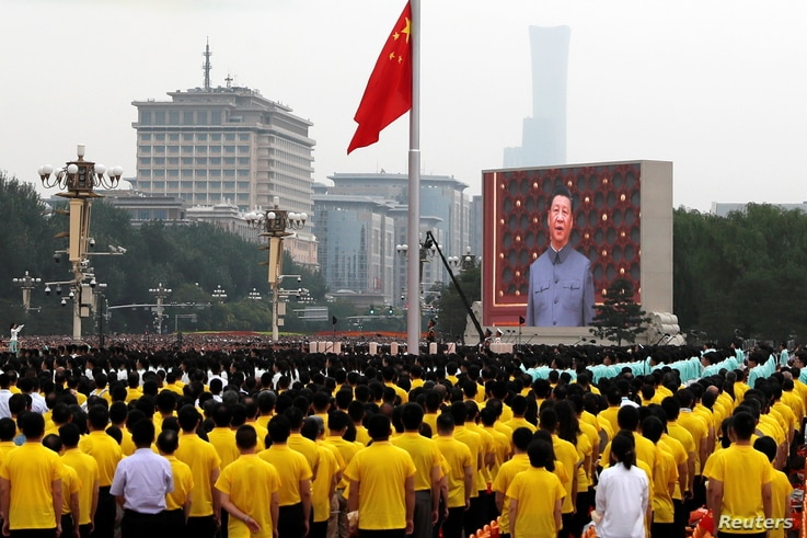 A giant screen shows Chinese President Xi Jinping singing the national anthem during a flag-raising ceremony at the event marking the 100th founding anniversary of the Communist Party of China, on Tiananmen Square in Beijing, China, July 1, 2021.