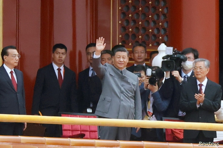 Chinese President Xi Jinping waves next to Premier Li Keqiang and former president Hu Jintao at the end of the event marking…