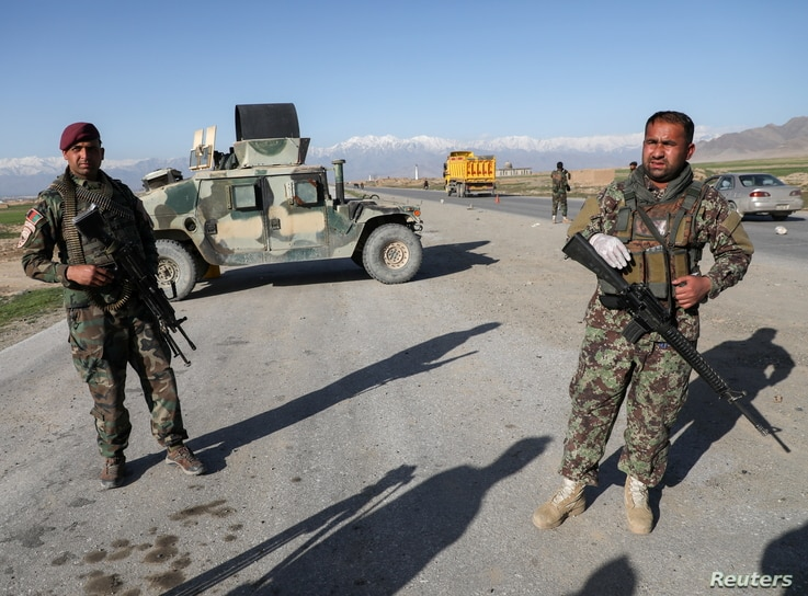 FILE PHOTO: Afghan National Army (ANA) soldiers stand guard at a check point near the Bagram Airbase north of Kabul,…