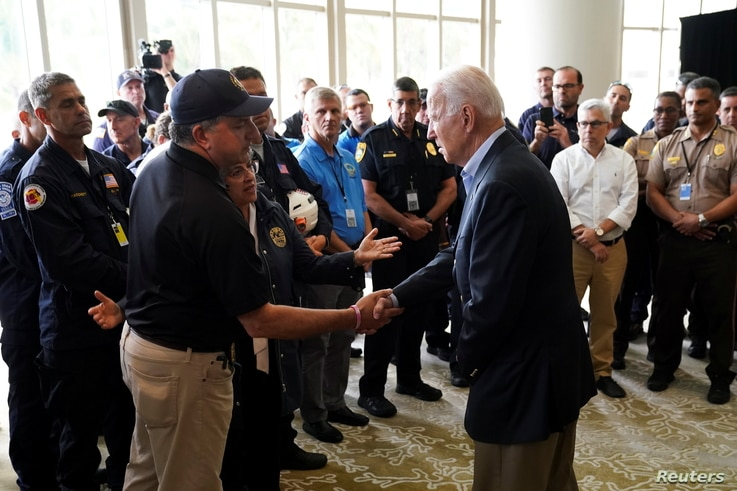 U.S. President Joe Biden shakes hands with Florida Chief Financial Officer Jimmy Patronis as he meets rescue teams and first…