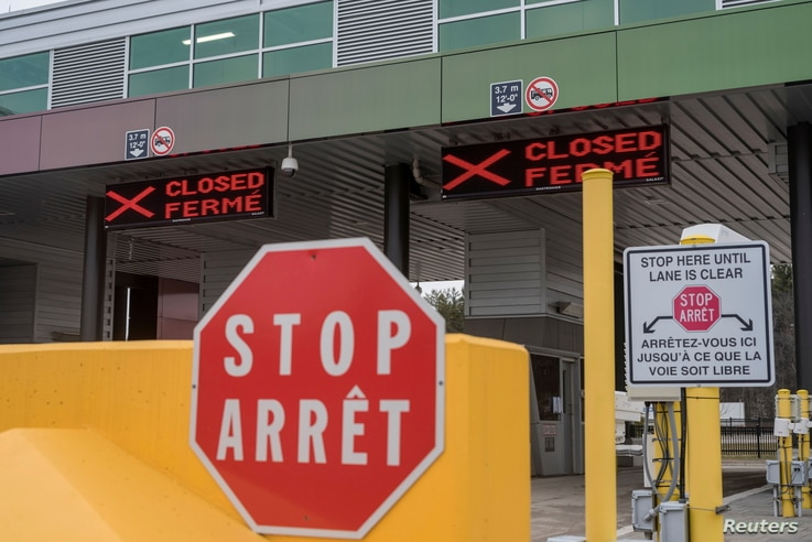 """FILE PHOTO: Two closed Canadian border checkpoints are seen after it was announced that the border would close to """"non…"""