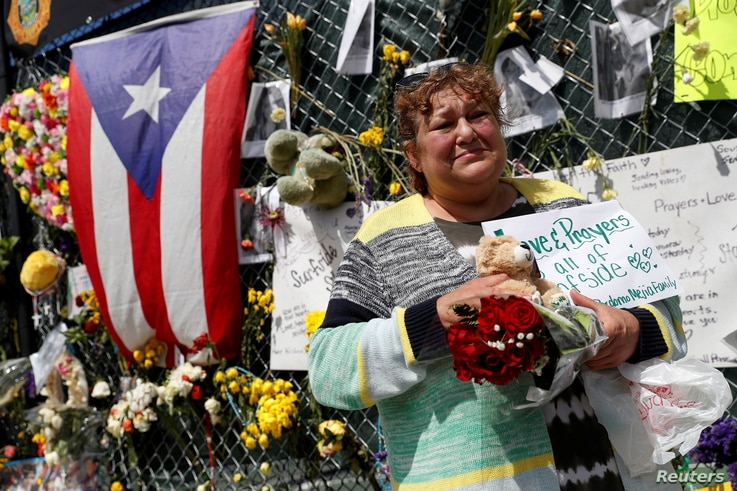 Maria Perdomo grieves by a makeshift memorial for the victims of the Surfside's Champlain Towers South condominium collapse in Miami, Florida, July 8, 2021.