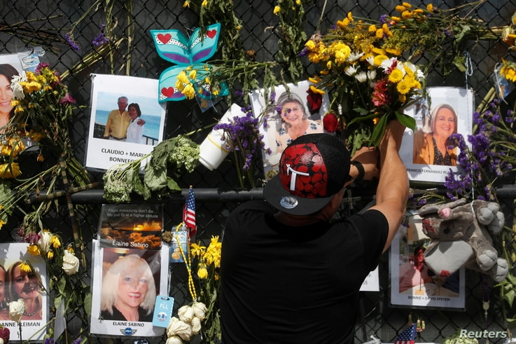 A man places flowers on a makeshift memorial for the victims of the Surfside's Champlain Towers South condominium collapse in Miami, Florida, July 8, 2021.