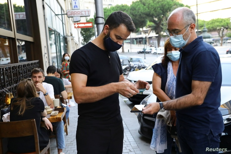 Restaurant staff checks a digital vaccination certificate at the entrance, on the day that Portugal's government imposed…