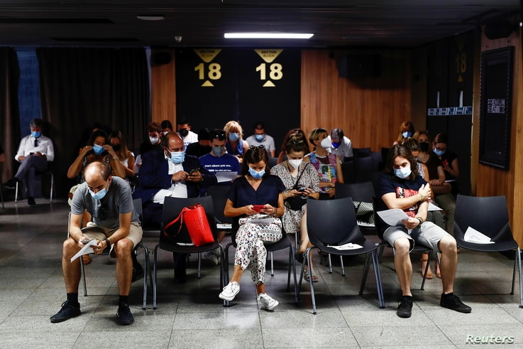 People sit after they received a coronavirus disease (COVID-19) vaccine as the country extends vaccination to curb surge among…