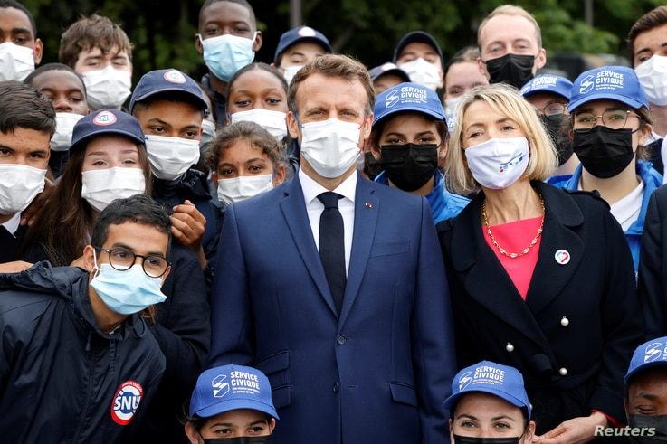French President Emmanuel Macron poses with volunteers of the Civic Service of the General National Service (SNU).