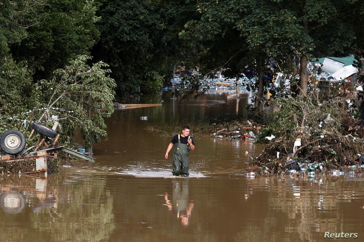 A man walks through the water in an area affected by floods following heavy rainfalls in Bad Neuenahr-Ahrweiler, Germany, July…