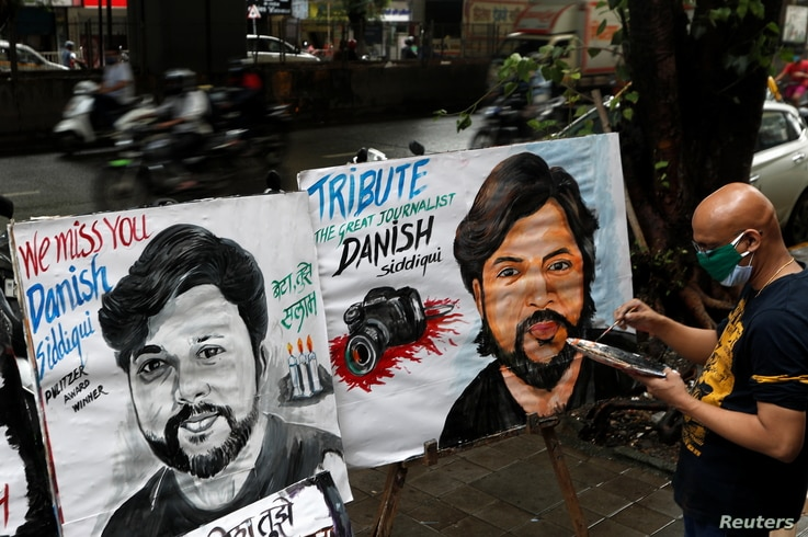 An artist applies finishing touches to a painting of Reuters journalist Danish Siddiqui, after he was killed while covering a…