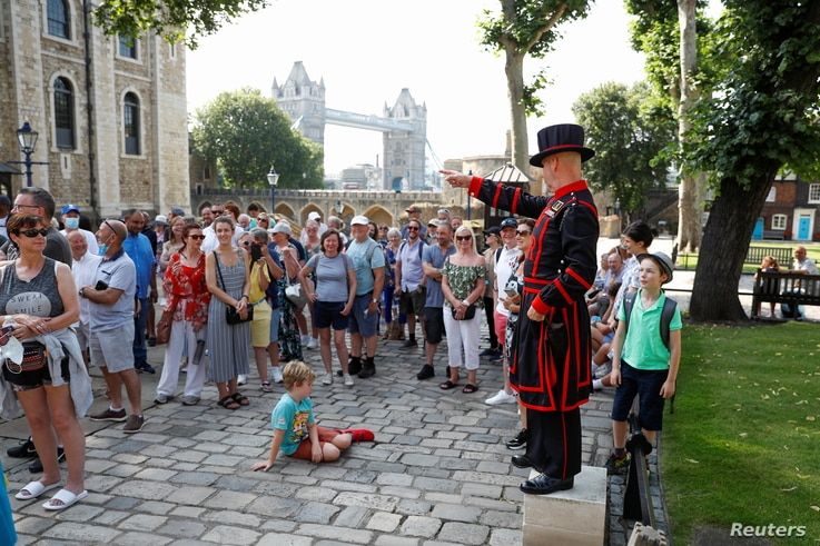 """A Yeoman Warder, Barney Chandler gestures as he leads the first """"Beefeater"""" tour of the Tower of London in 16 months, at the…"""