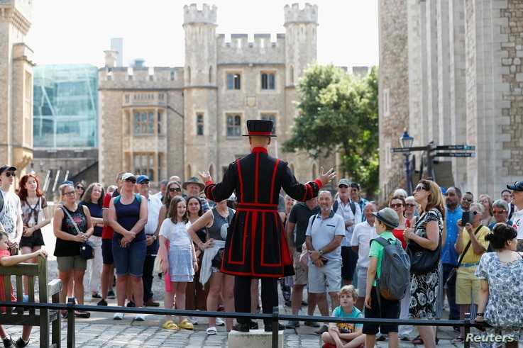 """A Yeoman Warder, Barney Chandler speaks to the group, as he leads the first """"Beefeater"""" tour of the Tower of London in 16…"""