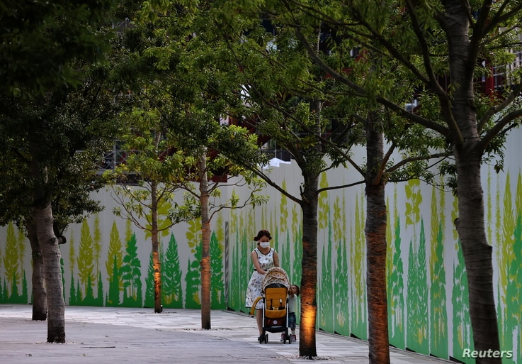 A woman wearing a protective mask, amid the coronavirus disease (COVID-19) outbreak, pushes a stroller outside the National Stadium, the main venue of the Tokyo 2020 Olympic Games in Tokyo, Japan, July 28, 2021.