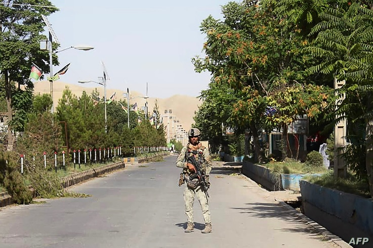 An Afghan security forces personnel stands guard along a road amid ongoing fighting with Taliban fighters in the western city of Qala-i- Naw, the capital of Badghis province, July 8, 2021.