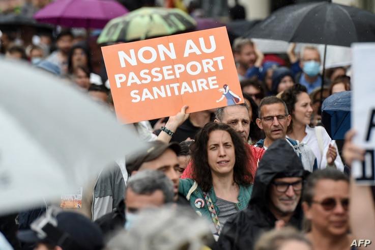 A woman holds a placard reading 'No to the health pass' during a demonstration against the compulsory vaccination for certain workers and the mandatory use of a health pass called for the French government, in Nantes, France, July 24, 2021.