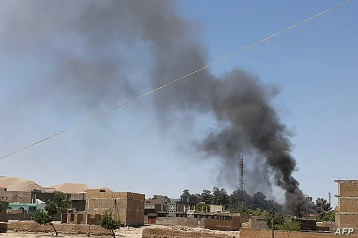 A plume of smoke rises amid ongoing fighting between Afghan security forces and Taliban insurgeents in the western city of Qala-e-Naw, the capital of Afghanistan's Badghis province, July 7, 2021.