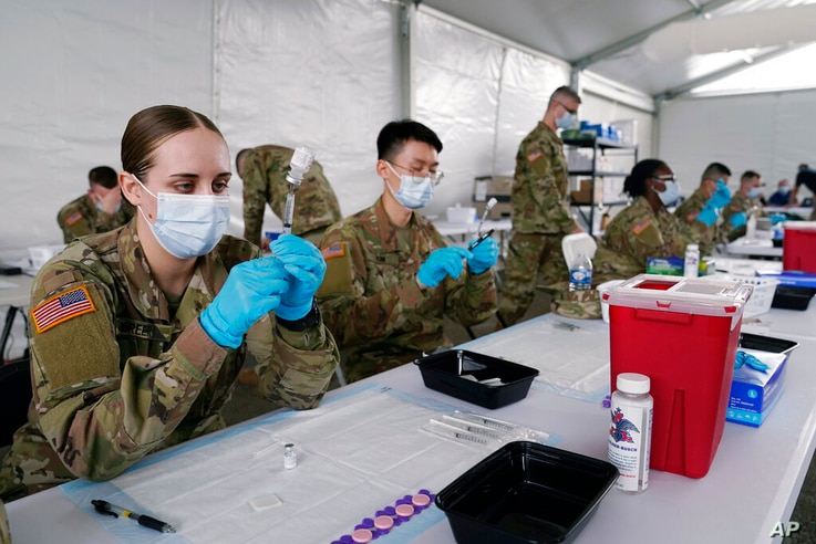 FILE - In this March 9, 2021, file photo, Army health specialists fill syringes with the Pfizer COVID-19 vaccine in Miami…