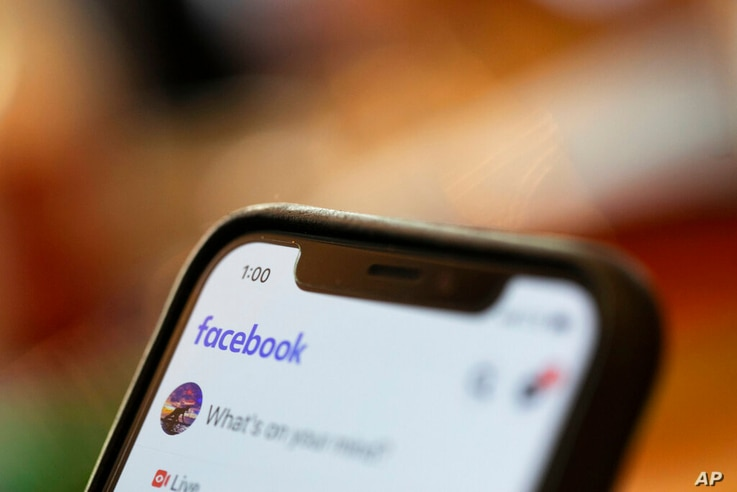 FILE - In this Aug. 11, 2019, file photo an iPhone displays a Facebook page in New Orleans.   Facebook says hackers in China…