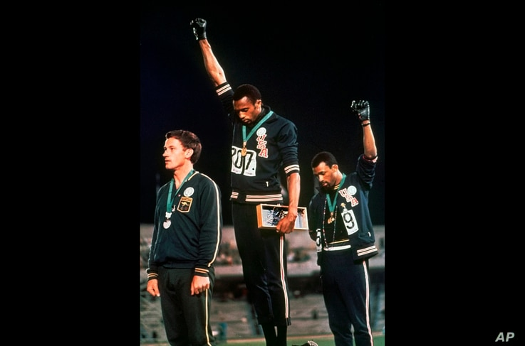FILE - In this Oct. 16, 1968 file photo, U.S. athletes Tommie Smith, center, and John Carlos raise their gloved fists after…