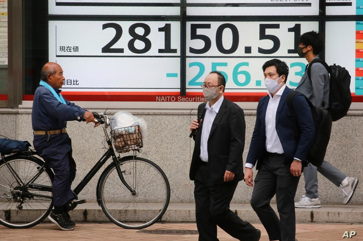 People walk by an electronic stock board of a securities firm in Tokyo, Wednesday, May 19, 2021. Asian shares fell Wednesday,…