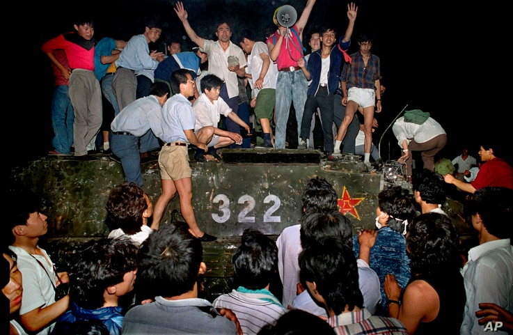 In this early June 4, 1989, file photo, civilians with rocks stand on a military armored vehicle near Chang'an Boulevard in…