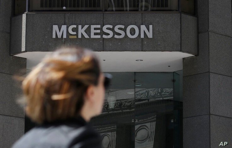 FILE - In this July 17, 2019, file photo, a pedestrian passes a McKesson sign on an office building in San Francisco.  The…