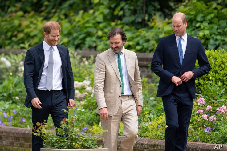 Britain's Prince William, right, and Prince Harry speak with garden designer Pip Morrison during the unveiling of a statue they commissioned of their mother Diana, Princess of Wales, in the Sunken Garden at Kensington Palace, London, on what would have been her 60th birthday, Thursday, July 1, 2021. (Dominic Lipinski/Pool Photo via AP)