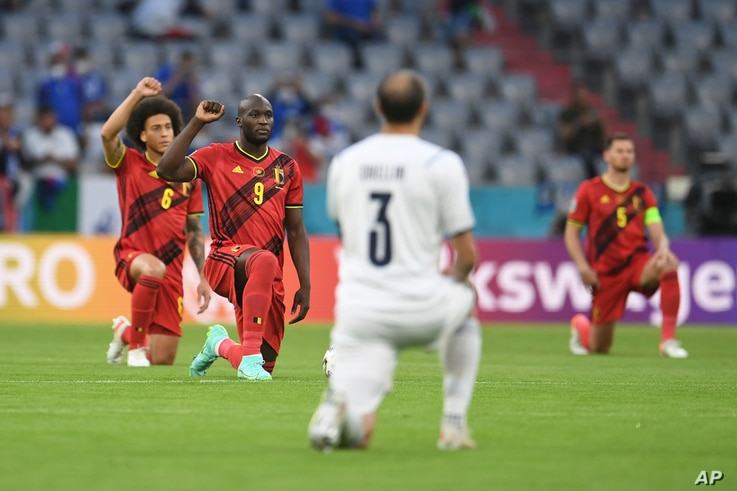 Players take a knee before a Euro 2020 soccer championship quarterfinal match between Belgium and Italy at the Allianz Arena in...