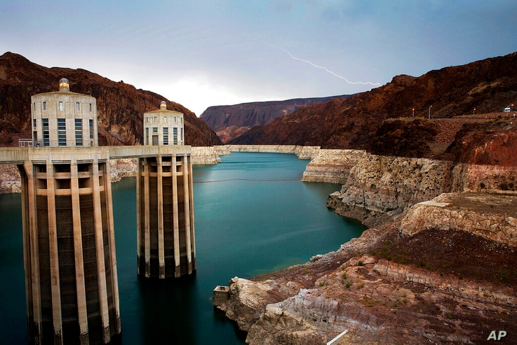 FILE - In this July 28, 2014, file photo, lightning strikes over Lake Mead near Hoover Dam that impounds Colorado River water…