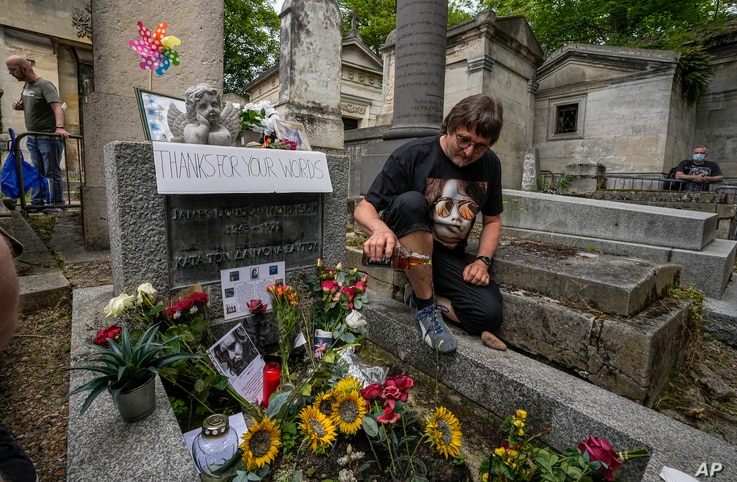Torsten Marquardt of Germany pours some whiskey on the tomb of rock singer Jim Morrison at the Pere-Lachaise cemetery in Paris,…