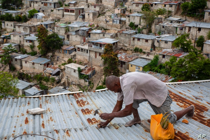 Antony Exilien secures the roof of his house in response to Tropical Storm Elsa, in Port-au-Prince, Haiti, Saturday, July 3,…