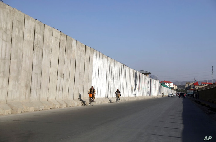 Afghan men ride their bicycles walk past blast walls protecting the ministry of interior affairs, in Kabul, Afghanistan,…