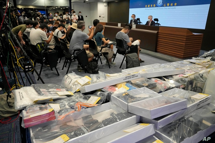 Police hold a news conference with confiscated evidence seen at front, the police headquarters in Hong Kong.
