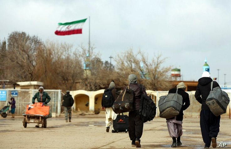 FILE- In This Feb. 20, 2019 photo, Afghans return to Afghanistan at the Islam Qala border with Iran, in the western Herat…