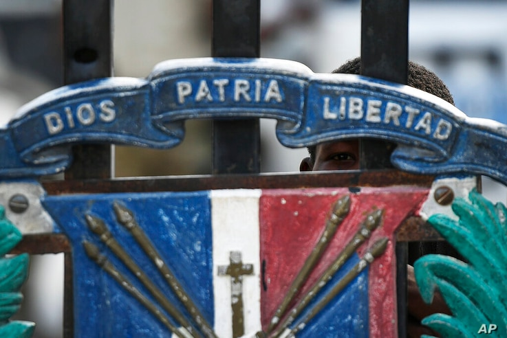 A youth peers though the closed gate at the border with Haiti in Jimani, Dominican Republic, Thursday, July 8, 2021. Dominican…